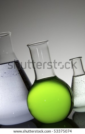 group of three laboratory flasks brightly colored liquid