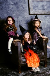 group of three little girl wearing in witch costumes celebrate Halloween indoor
