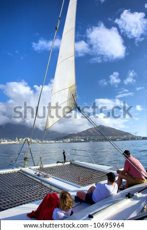 Group of three people on catamaran's desk during sea cruise. Shot near Waterfront, Cape Town, Western Cape, South Africa.