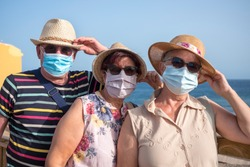 Group of three senior people wearing medical mask because of coronavirus hold their hat while enjoying freedom and sea excursion - active elderly adult during retirement