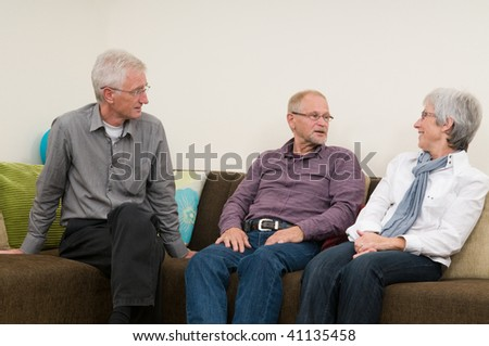 Group of three seniors talking and laughing on a couch at home.