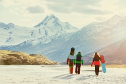 Group of three snowboarders walking on background of glacier. Ski tourism concept