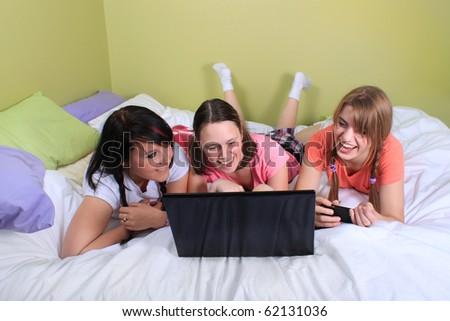 Group of three teenage girls with pigtails and braided hair having a slumber party or sleepover laying on a bed using a laptop and cellphones