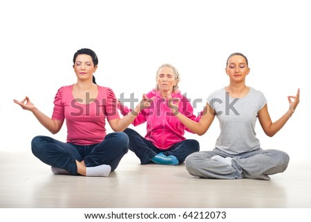 Group of three women in lotus yoga position on floor over white background