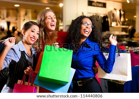 Group of three women - white, black and Asian - shopping downtown in a mall