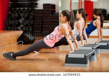 Group of three women working out together in a class at a gym