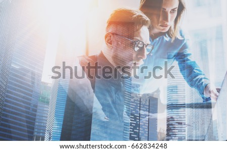 Group of three young coworkers working together at modern coworking office.Teamwork concept.Double exposure,skyscraper building blurred background.Flares effect.Horizontal