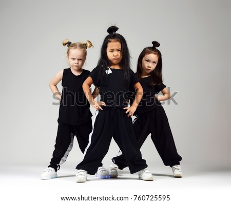 Group of three young girl kids hip hop dancers on gray background