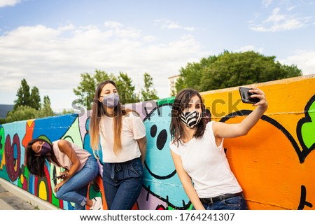 Group of three young girls having fun, taking selfie and wearing trendy face masks for protection against covid-19 coronavirus new normal concept social distancing