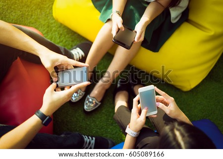 Group of three young people using smartphones together, modern lifestyle or communication technology gadget concept.
