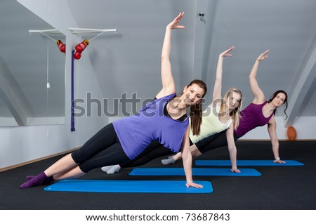 Group of three young women doing exercises in a fitness club