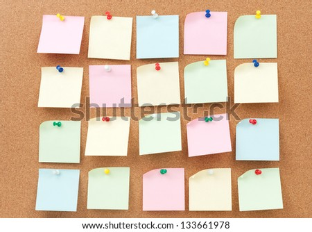 Group of thumbtack and note paper on cork board