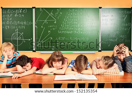 Group of tired school children at a classroom. Education.
