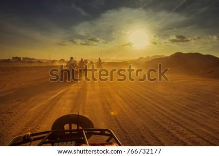 Group of tourist on ATV in Egypt desert during sundown. Toned, rework. Stock photo ©