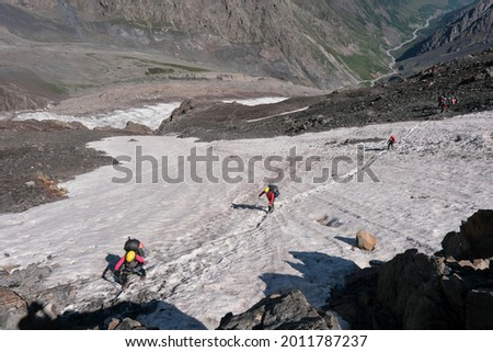 Group of tourists crosses a snowfield on the slope of Mount Kazbek on sunny summer day. North Ossetia, Caucasus, Russia. Stock photo ©