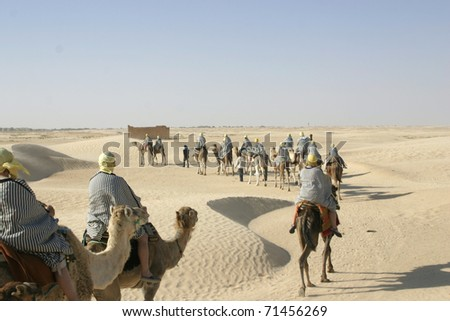 Group of tourists dressed like bedouins riding camels in line thorough Sahara desert in Tunisia - stock photo
