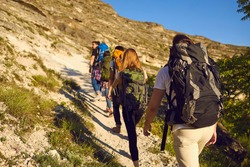 Group of tourists hikers climbing natural rocks with backpacks in row during summer vacations on sunny clear day, rear view. Hiking and traveling together