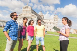 Group of tourists in Pisa, Italy. A group of friends is listening to a guide talking about a famous monument. They are a multicultural group on holidays, with travel and architecture concepts