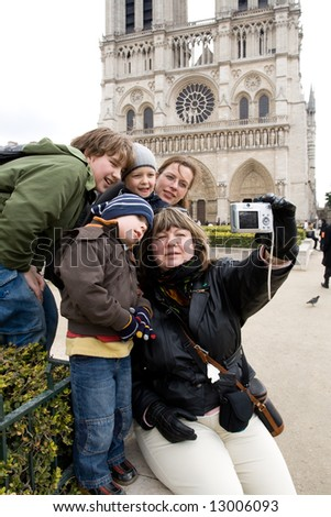 Group of tourists, members of one family taking self portrait at the famous Cathedrale Notre-Dame de Paris
