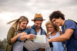 Group of tourists searching for places on their map outdoors.