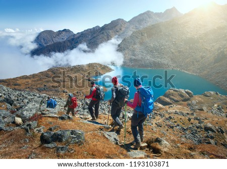 Group of tourists with backpacks descends down mountain trail to lake during hike in the national park Lantang, Nepal. Beautiful inspirational landscape, trekking and activity.