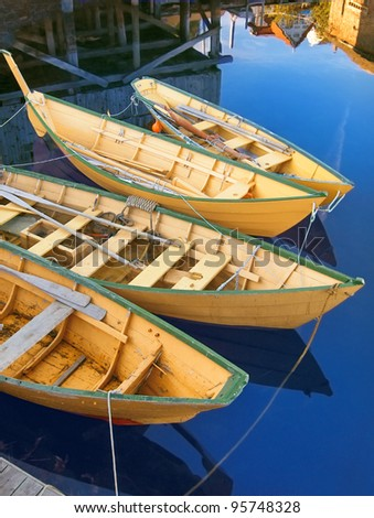 Group of traditional bright yellow painted wooden fishing dories roped together and moored at a dock in Lunenburg, Nova Scotia. Reflections of boathouses nearby. Vertical layout.
