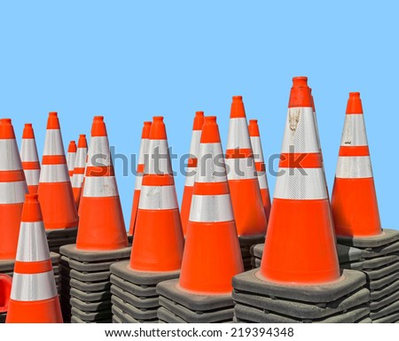 Group of traffic cones stacked and nested together. Plastic orange and white reflective safety cones with black base. Isolated on blue background.