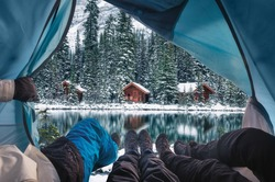 Group of traveler opening tent with wooden lodge in snow forest on Lake O'hara at Yoho national park, Canada