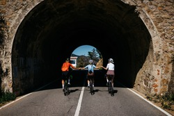 group of tree cyclist hold hands at the tunnel riding bicycle. fun ride with a friend at farm summer day. people enjoy cycling. healthy lifestyle, fun time