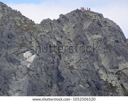 Group of trekkers on the top a mountain on the craggy ridge separating Poland and Slovakia, High Tatry