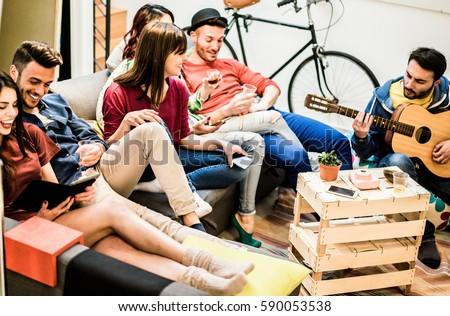 Group of trendy friends having fun in home living room - Happy young people enjoying time together playing music and watching videos with tablet - Main focus on center girl face