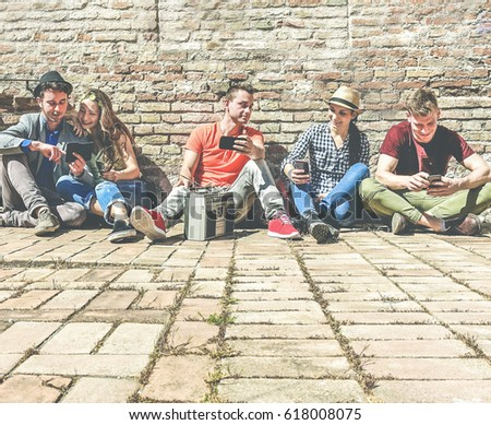 Group of trendy friends using mobile cell phones and listening music in old historical town center outdoor - Technology mania of new generation concept - Young people having fun - Warm contrast filter #618008075
