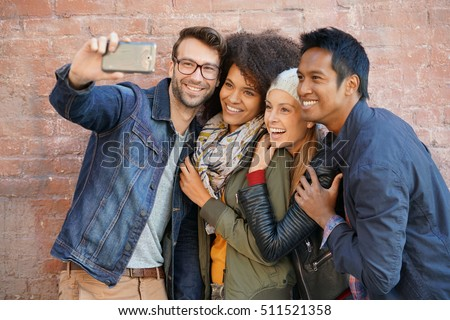 Group of trendy people taking selfie picture, brick wall background