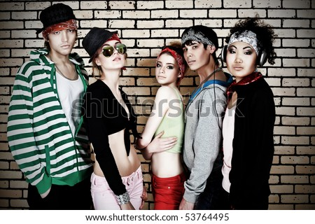 Group of trendy teenagers posing together against a brick wall.