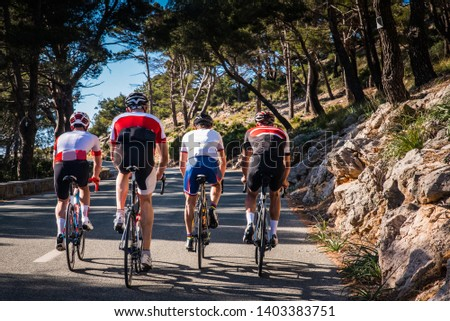 Group of triathletes on road bicycle, sport photo in nature. Majorca, Spain #1403383751