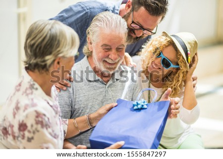 group of two seniors and two adults at the mall together - three people giving a present at the mature man for his birthday or for christmas #1555847297