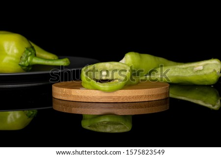 Group of two whole two halves two slices of hot green pepper banana on round bamboo coaster on gray ceramic plate isolated on black glass #1575823549