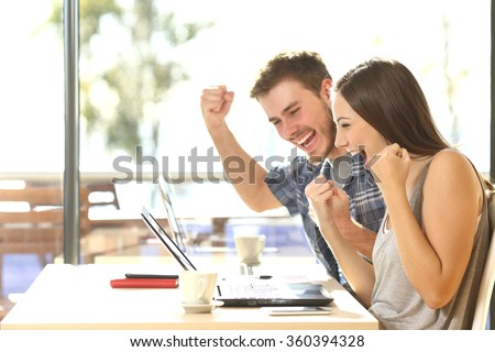 Group of two young euphoric students watching exam results in a laptop in a table of an university campus bar