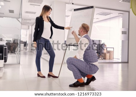 group of two young people, businessman and pregnant businesswoman, bussiness meeting presentaion, showing on board ideas concepts. modern building office. #1216973323