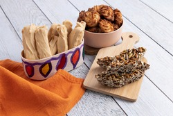 Group of typical Guatemalan sweets on a light wooden background, with orange napkin with kitchen containers