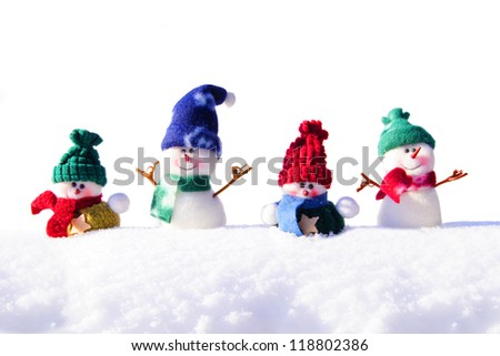 Group of unique snowmen decorations in resting in fresh snow