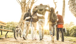 Group of urban friends walking in city skate park with backlighting at sunset - Youth and friendship concept with multiracial young people having fun together - Warm retro filter with soft focus