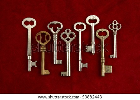Group of various shaped and colored skeleton keys shot on red suede background