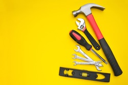 Group of various tools on yellow background with space for texts