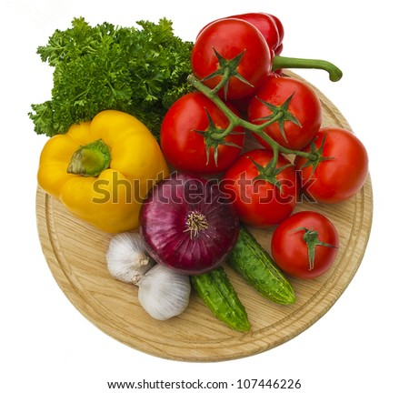 Group of vegetables on cutting board isolated over white