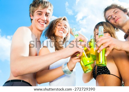 Group of very beautiful people celebrating on the beach in the summer of their lives