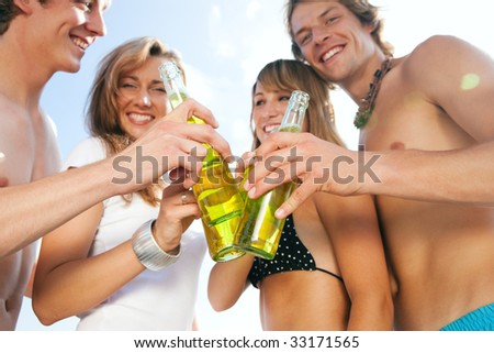 Group of very beautiful people celebrating on the beach in the summer of their lives - focus on bottles