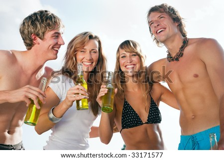 Group of very beautiful people celebrating on the beach in the summer of their lives - focus on faces