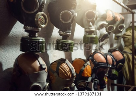 Group of vintage old gas masks on wall in bomb shelter, close up