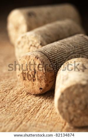 Group of vintage wine corks on old wooden surface.